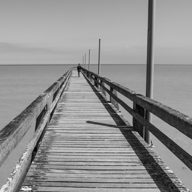 """Lone figure on wooden pier"" stock image"