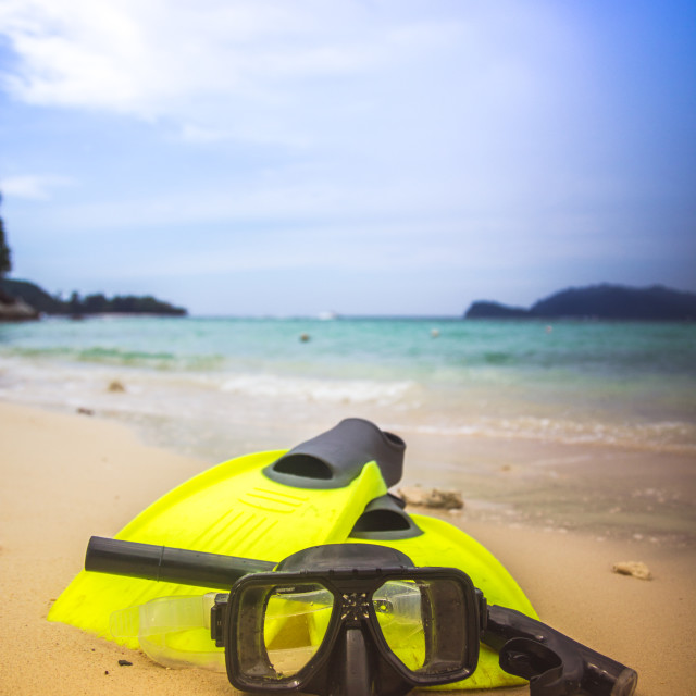 """Snorkelling gear lies on beach sand near ocean"" stock image"
