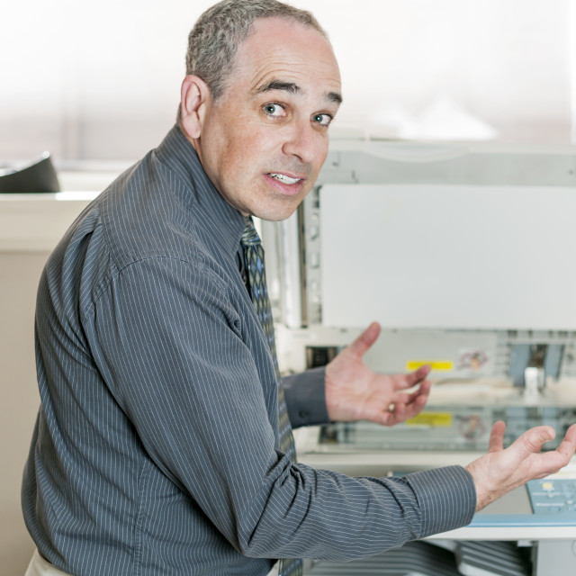 """""""Man frustrated with photocopier"""" stock image"""