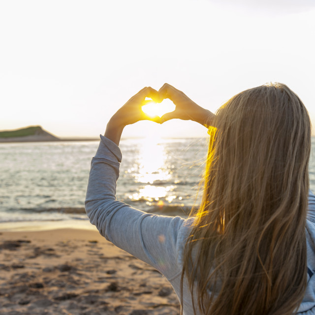 """Girl holding hands in heart shape at beach"" stock image"