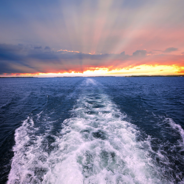 """""""Sunset over ocean with boat wake"""" stock image"""
