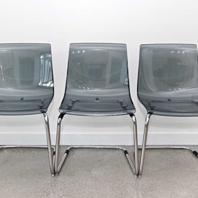 """""""Three plastic chairs against wall"""" stock image"""