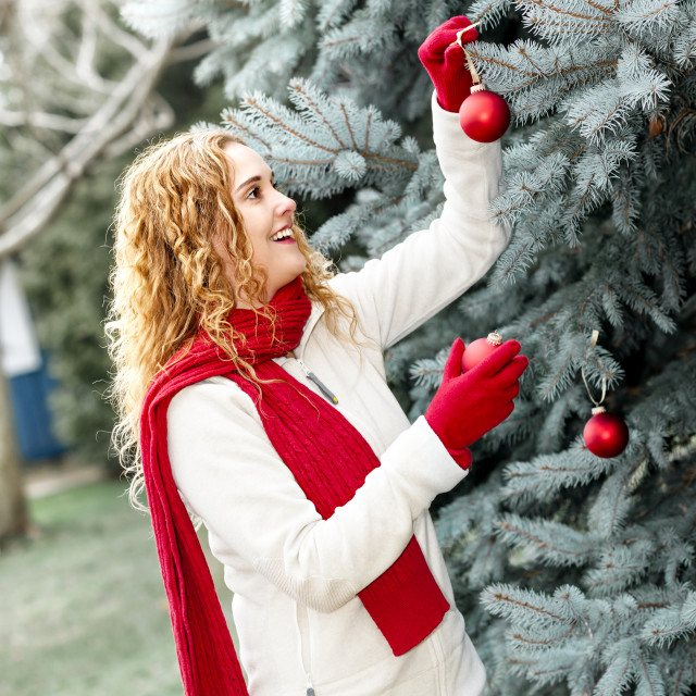 """Woman decorating Christmas tree outside"" stock image"