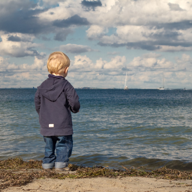 """""""Little boy at a beach looking towards the sea in autumn"""" stock image"""