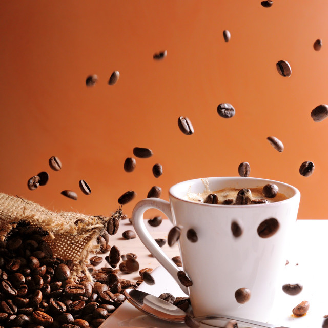 """Coffee beans falling on table with coffee cup"" stock image"