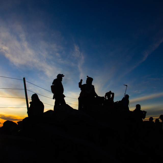"""Hikers on top of mountain at sunrise / sunset"" stock image"