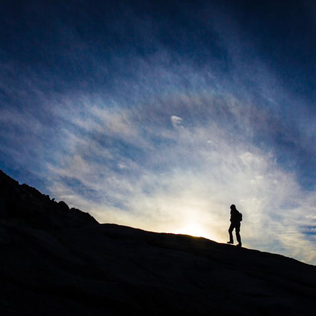 """woman walking on mountain silouhetted by sunrise or sunset"" stock image"