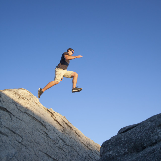 """A Man Jumping Off A Large Boulder"" stock image"
