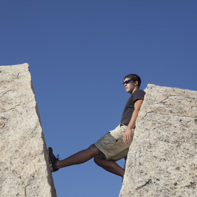 """Man Resting in a Crevice Between Two Boulders"" stock image"