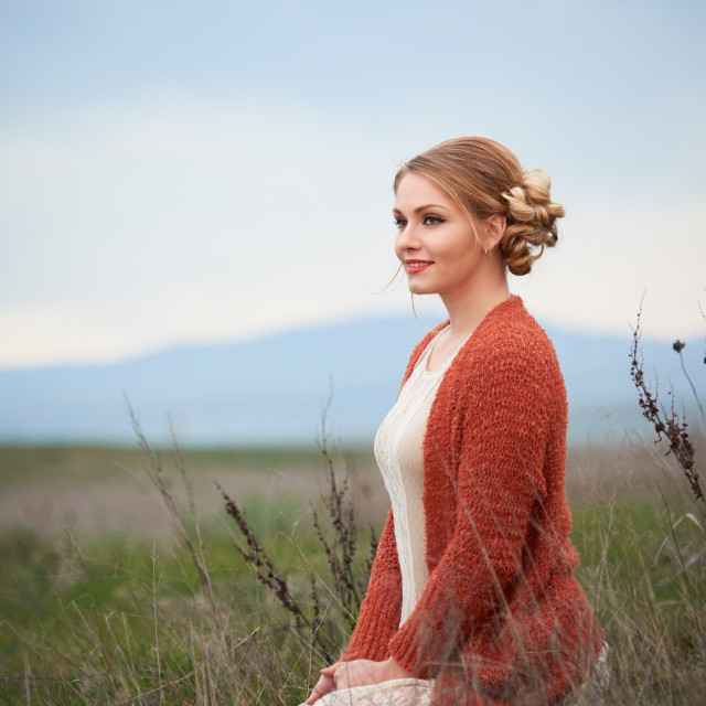 """Woman in a Dress Standing in a Field"" stock image"