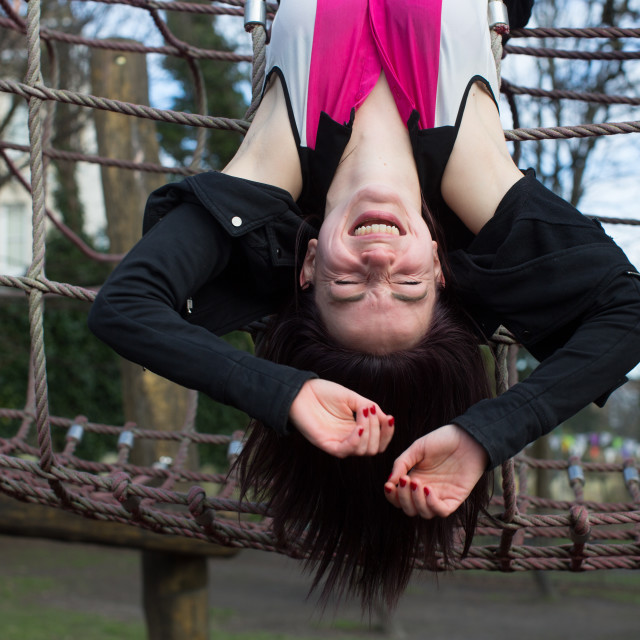 """Teenage Girl Hanging Upside Down on Jungle Gym"" stock image"