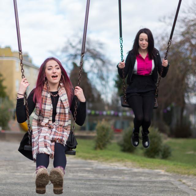 """Two Teenage Girls Swinging on Swings"" stock image"
