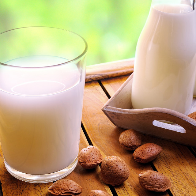 """""""Glass of almond milk on a table with almonds"""" stock image"""