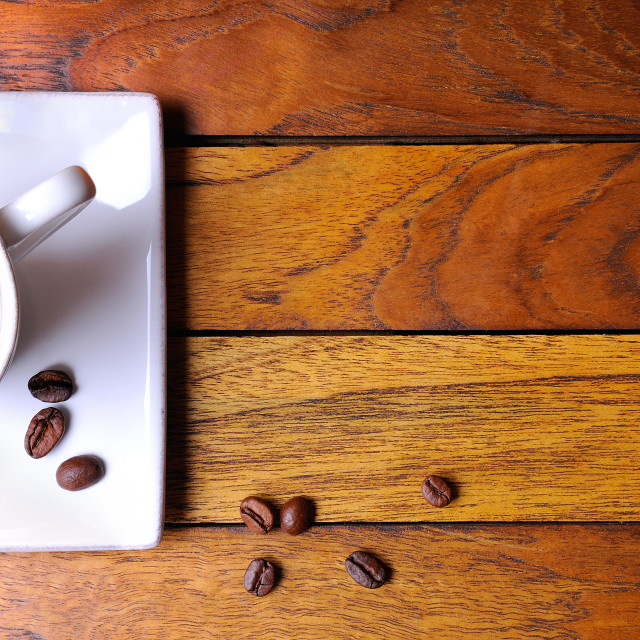 """Cup of coffee and beans on a brown wooden table"" stock image"