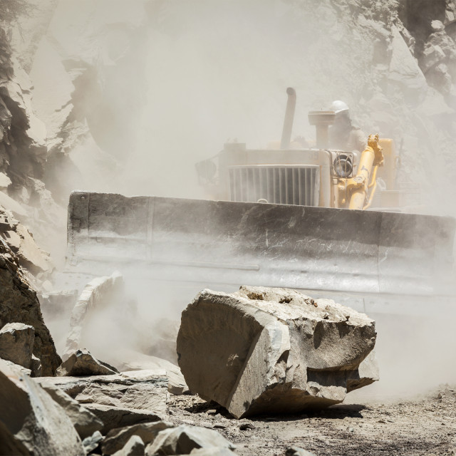 """Bulldozer cleaning landslide on road in Himalayas"" stock image"