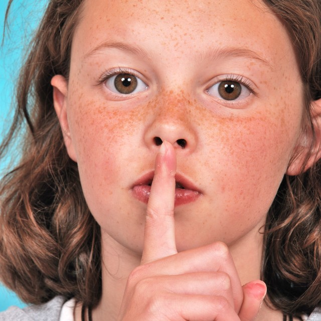 """""""Young woman making silence finger over her mouth"""" stock image"""