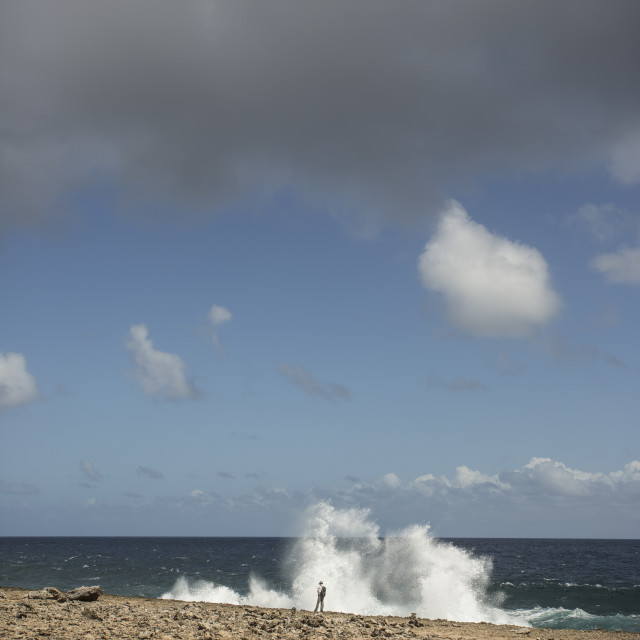 """Lone hiker dwarfed by a wave, Curacao,"" stock image"
