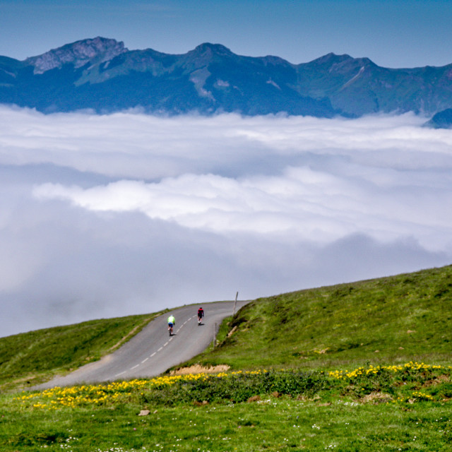 """Distant cyclists in pyrenees cloud"" stock image"