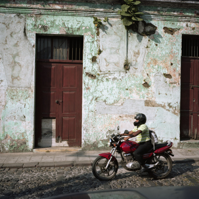 """Motorcycle passes wall with texture, Guatemala"" stock image"