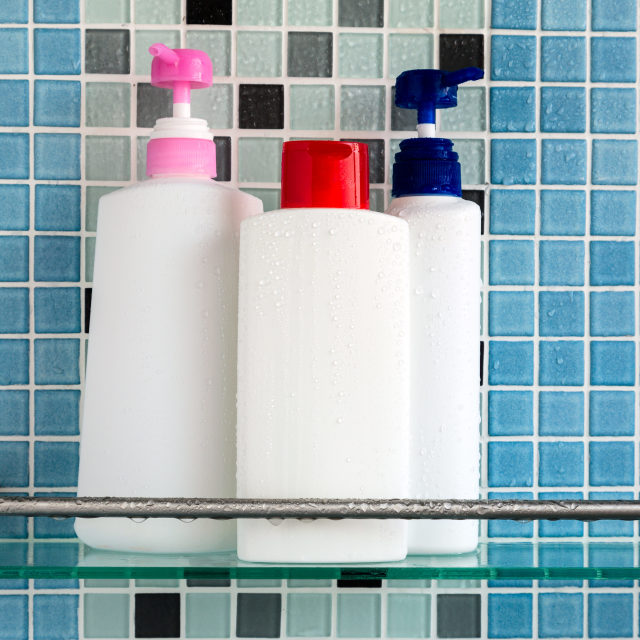 """Group of shampoo bottles in a bathroom"" stock image"