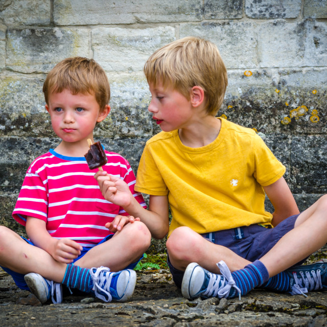 """Two boys sharing an ice lolly"" stock image"