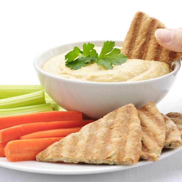 """Hand dipping pita in hummus"" stock image"