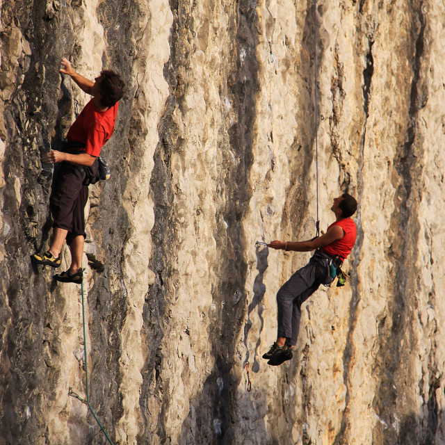 """Two climbers practicing alpinism on vertical stone wall"" stock image"