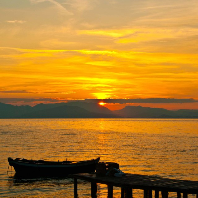 """""""Boat moored on jetty against rising sun"""" stock image"""
