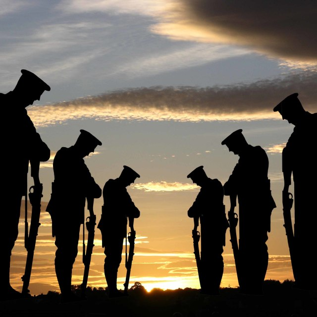 """Silhouette of soldiers during rememberence against the sunset"" stock image"