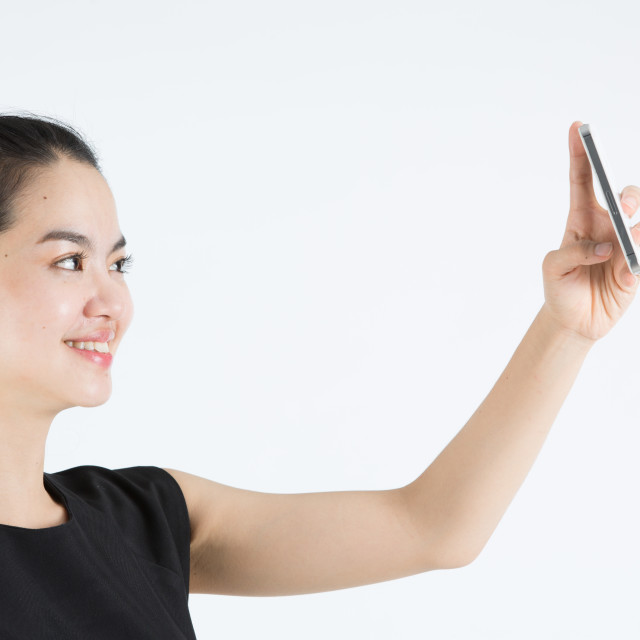 """""""Young asian lady taking a selfie"""" stock image"""