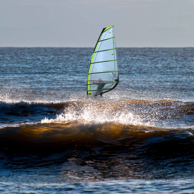 """""""Wind surfing on rough waves at Llantwit Major beach"""" stock image"""