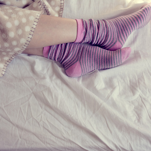 """girl with pink striped socks, sleeping in bed"" stock image"