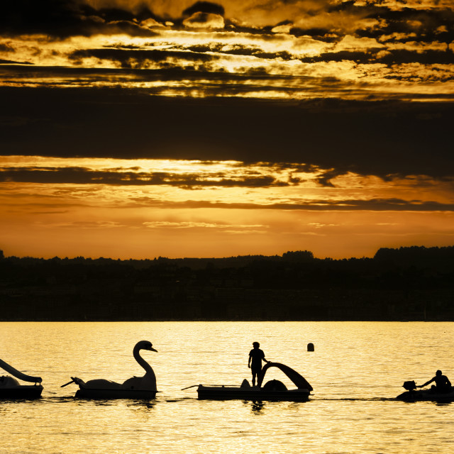 """""""pedal boats navigate on the beach at sunset"""" stock image"""