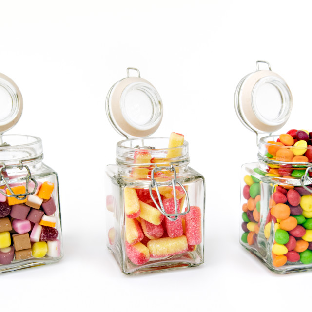 """Mixture of sweets in three open glass jars"" stock image"