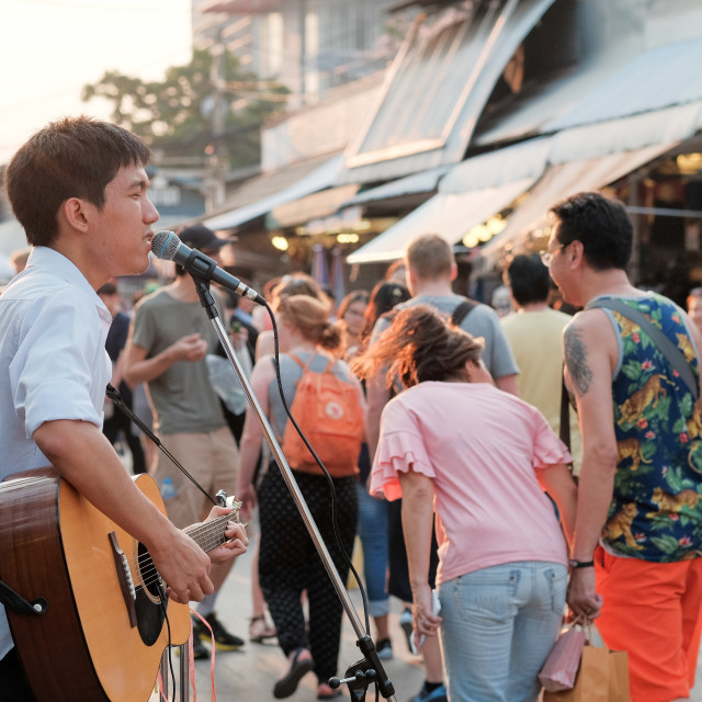 """Bagkok, Thailand - Circa March 2015: Unidentified youung man sings at the Chatujak weekend market. Chatujak is the largest weekend market in Bangkok."" stock image"