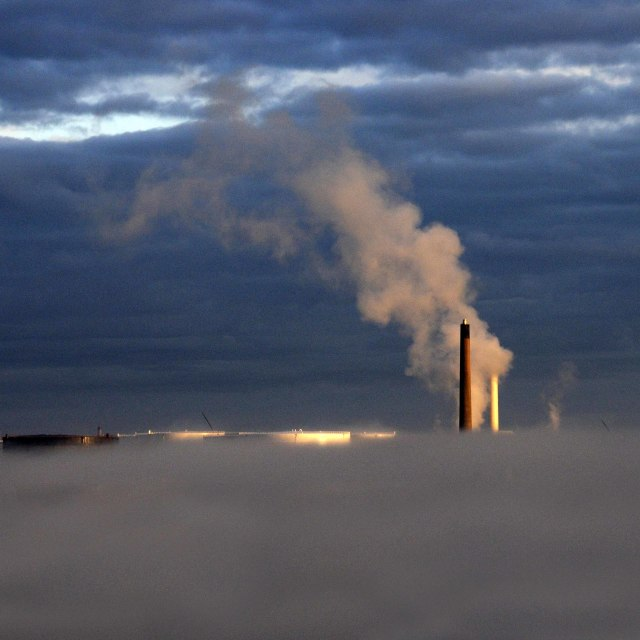 """""""Morning mist beneath a smoking chimney stack in an oil refinery"""" stock image"""