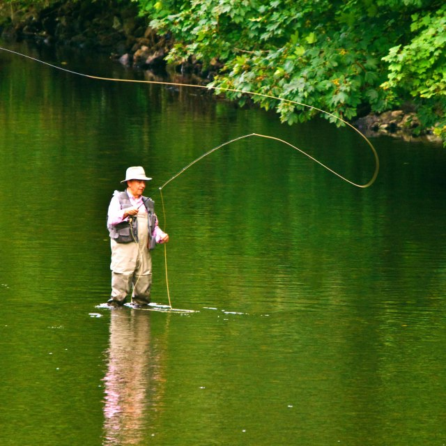 """Man casting a fishing rod in the river Tawe at Pontatdawe"" stock image"