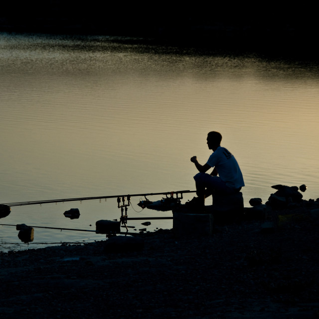 """Silhouette of a fisherman at the side of a lame."" stock image"