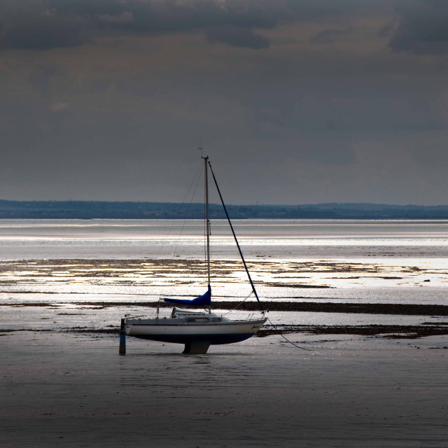 """Beached yacht on tidal estuary"" stock image"