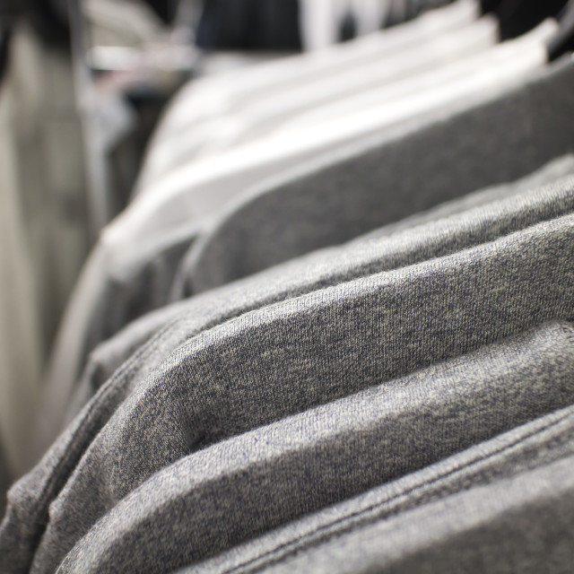 """t-shirts on rack at clothing store"" stock image"