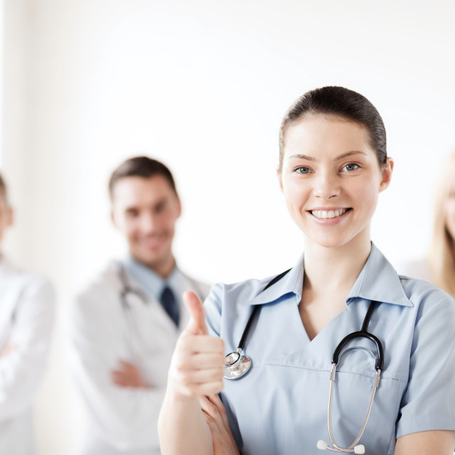 """doctor with group of medics showing thumbs up"" stock image"
