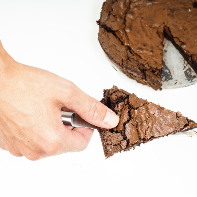 """Person holding up a piece of freshly made chocolate cake"" stock image"