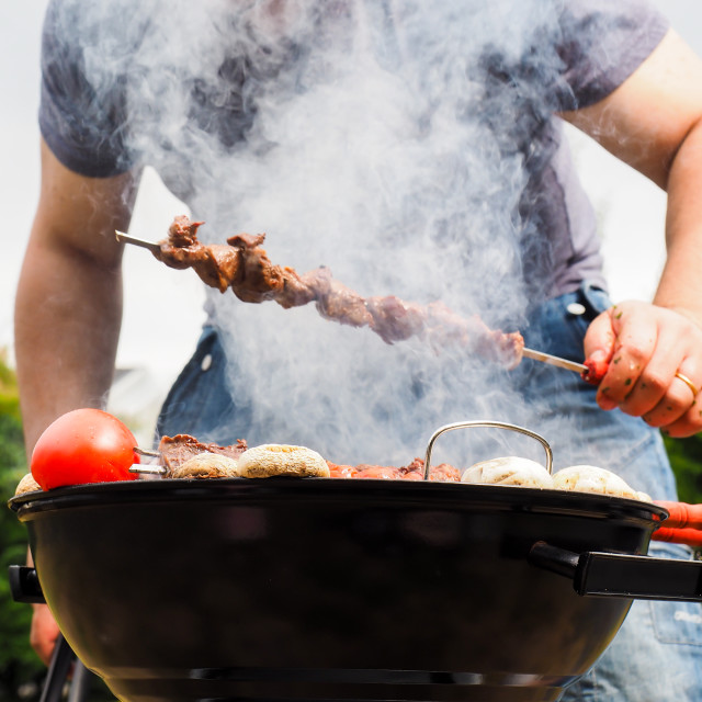 """Chef covered in smoke grilling skewers of meat and vegetables over charcoal barbecue"" stock image"