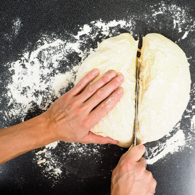 """""""Hands cutting a lump of dough into two pieaces on black table with flour spread"""" stock image"""