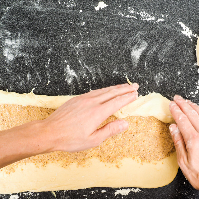 """Person rolling a snail bun with sugar and cinnamon spread"" stock image"