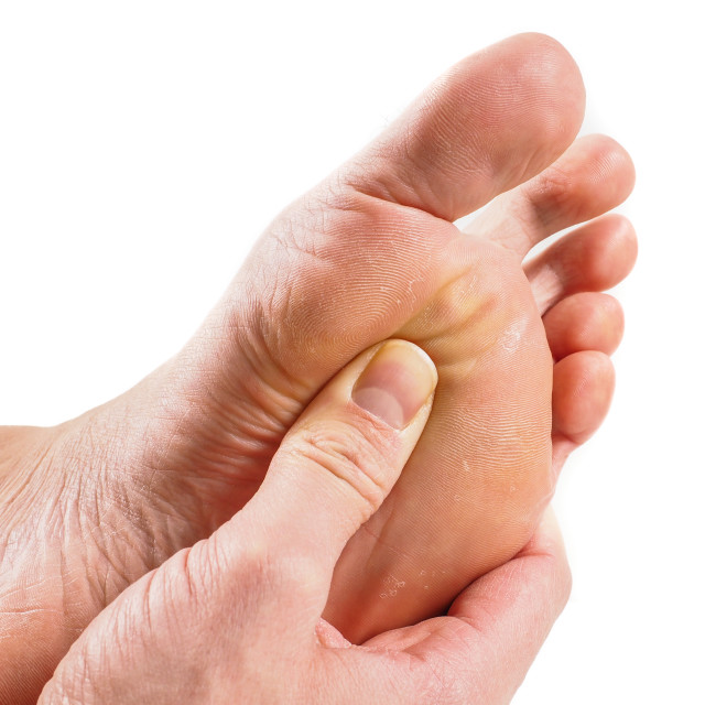 """Male person receiving podiatry with pressure point technique under foot isolated towards white"" stock image"