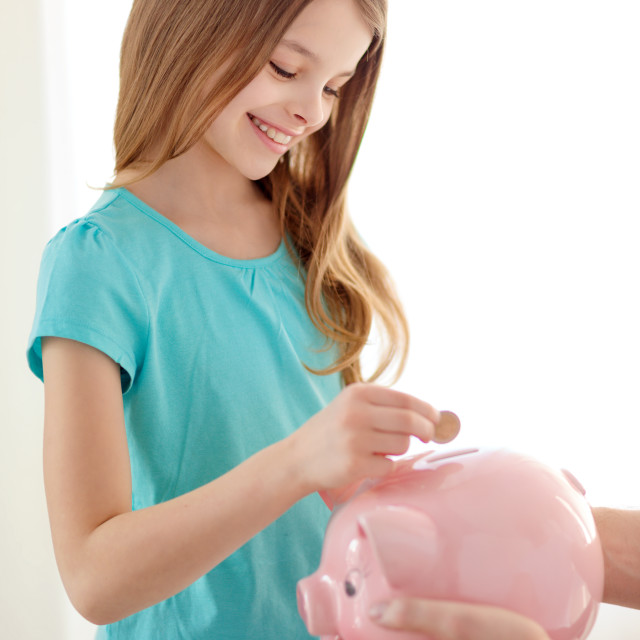 """""""smiling little girl putting coin into piggy bank"""" stock image"""