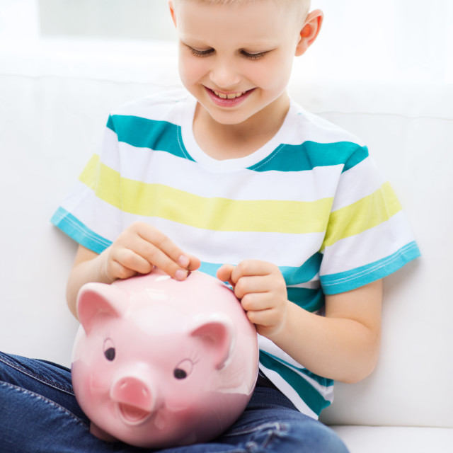 """""""smiling little boy with piggy bank and money"""" stock image"""