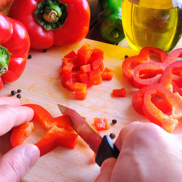 """Chef cutting a red pepper on a cutting board"" stock image"