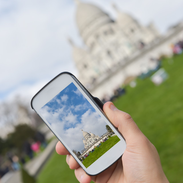 """""""Hands holding phone, making photo of Sacre Coeur."""" stock image"""